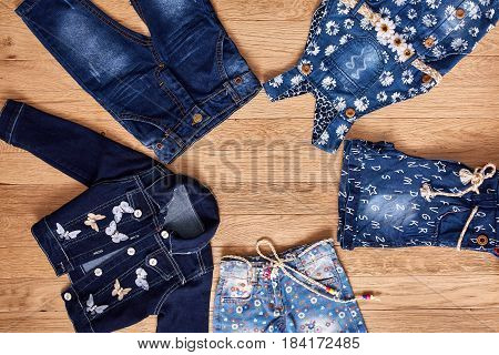 Children's jeans, jacket, denim shorts and denim dress on wooden background. Blue denim jacket, blue jeans in flowers and denim dress in flowers with cute belt. Clothes for little girl. Casual and modern chidren's style.