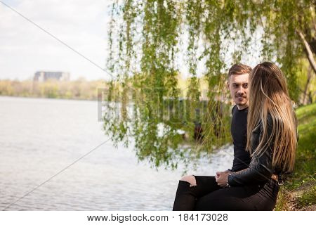 Young Couple on th edge of lake posing at camera. In love and relationship. Happines and love