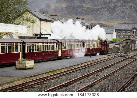 Blaenau Ffestiniog Wales UK - April 27 2017: A narrow gauge steam locomotive pulls out the station on track which first opened in 1836 the Ffestiniog Railway Company is the oldest surviving rail company in the world