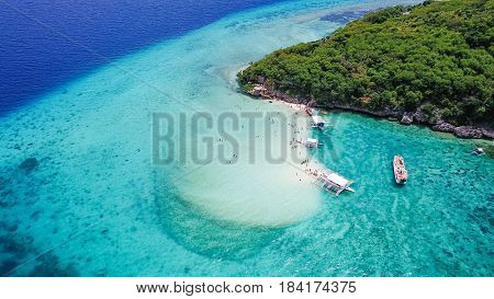 Aerial view of sandy beach with tourists swimming in beautiful clear sea water of the Sumilon island beach landing near Oslob Cebu Philippines. - Boost up color Processing.