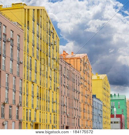 Fragment of a multicolored facade of the modern multi-story apartment complex against the background of the sky with clouds