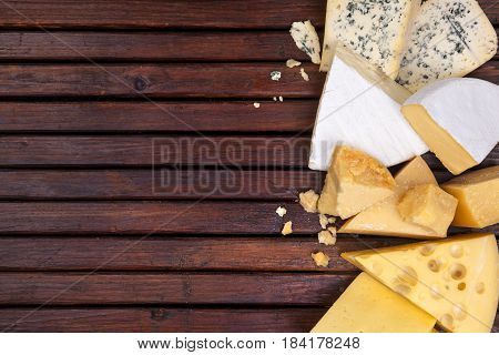 Various types of cheese on wooden table background. Cheddar, parmesan, emmental, blu cheese. Top view, copy space.