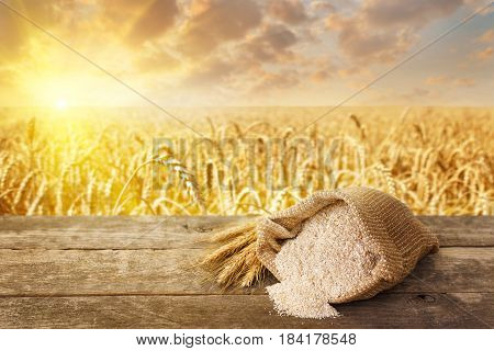 bran in bag and ears on table with ripe cereal field on the background. Food supplement to improve digestion. Dietary fiber. Product for healthy nutrition and diet. Golden field on sunset