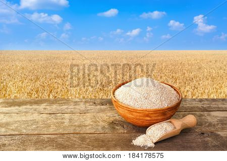 bran in bowl with wooden scoop on table with ripe cereal field on the background. Food supplement to improve digestion. Dietary fiber. Product for healthy nutrition. Golden field with blue sky