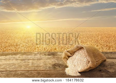 bran in sack on table with ripe cereal field on the background. Food supplement to improve digestion. Dietary fiber. Product for healthy nutrition and diet. Golden field on sunset