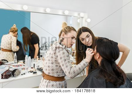 Makeup lesson at beauty school. Professional makeup artist conducts a master class. Make-up artist work in her studio. Real people. Visagiste applying makeup
