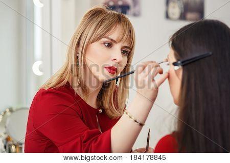 professional makeup artist doing makeup for young girl. Eye makeup. Closeup portrait of make-up artist at work in her studio. Real people. Backstage photo as visagiste applying makeup