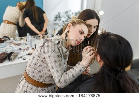 professional makeup teacher with her student girl. Makeup tutorial lesson at beauty school. Make-up artist work in her studio. Portrait of visagiste applying makeup on the eyes. Master class