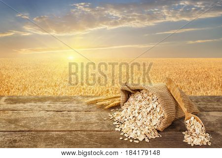 Oat flakes in bag. Still life scattered oatmeal, wooden spoon and ears on table with ripe cereal field on the background. Golden field on sunset. Healthy eating for diet and vegan