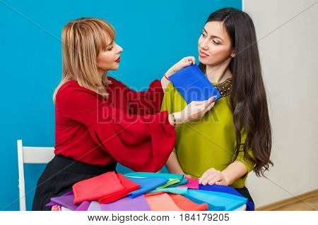 stylist doing color analysis of appearance for young woman. Image maker determines the colors that best suit an individual based on client natural colorings. Stylist working with client