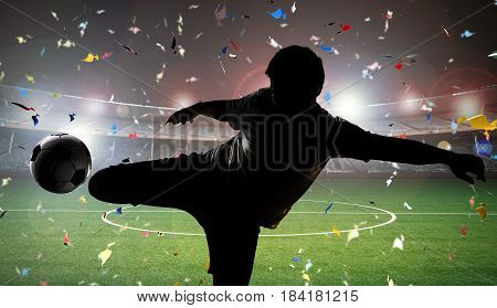 silhouette soccer player kicking the ball with field background