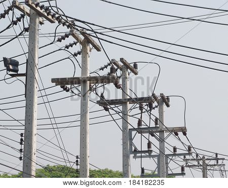 Row of concrete electricity poles with cross beams, insulators, and multidirectional wires.