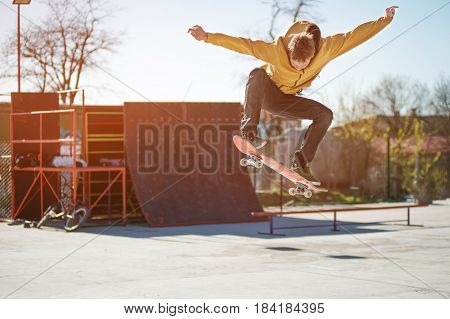 A teenager skateboarder does an ollie trick in a skatepark on the outskirts of the city Against the background of kickers