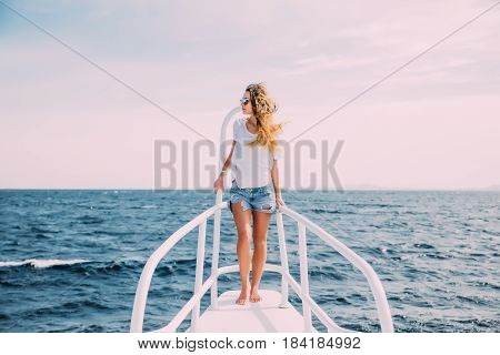 Beautiful Woman Standing On The Nose Of The Yacht At A Sunny Summer Day, Breeze Developing Hair, Bea