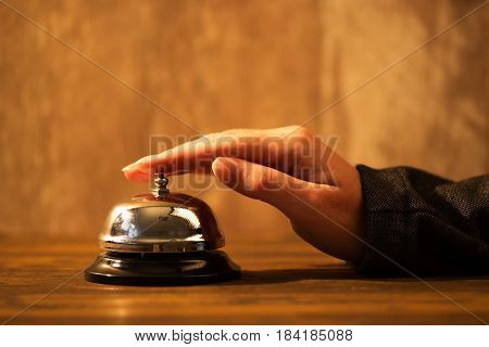 Businesswoman ringing hotel reception bell warm retro toned image with selective focus