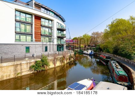 Waterside apartments at Limehouse Cut in London with Docklands Light Railway passing in the background