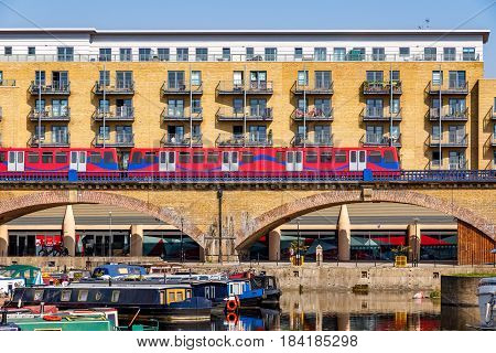 Waterside apartments at Limehouse Basin Marina in London with Docklands Light Railway passing by