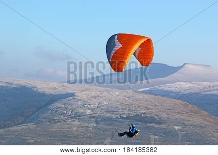 Paraglider flying in the Brecon Beacons in winter