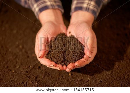 Handful of arable soil in hands of responsible female farmer close up selective focus