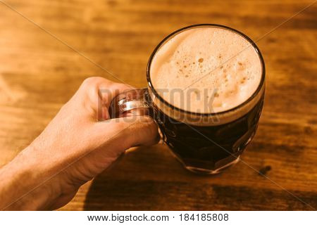 Man drinking dark beer in british dimpled glass pint mug on bar table