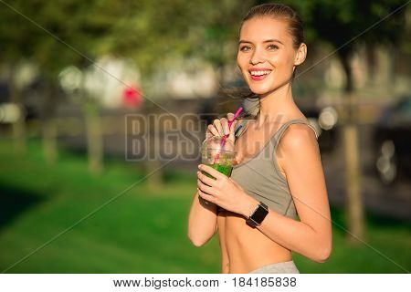 Young blonde woman walking drinking healthy green smoothie detox outdoors