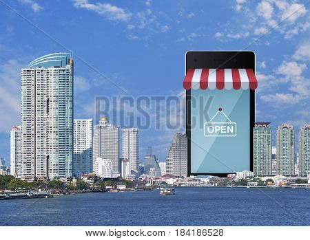 Modern smart mobile phone with on line shopping store sign modern office city tower river and blue sky e-business concept