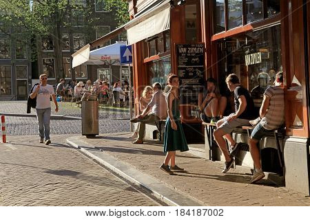 AMSTERDAM, NETHERLANDS - MAY 8, 2016: Young people in outdoor café at the street in historic center of Amsterdam, Netherlands.