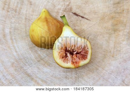 Common fig fruits cut open showing the flesh on wooden background, Top view.