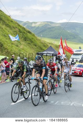 Col de PeyresourdeFrance- July 23 2014: Group of cyclists including Bernhard Eisel of Team Sky and Bryan Coquard of Team Europcar climbing the road to Col de Peyresourde in Pyrenees Mountains during the stage 17 of Le Tour de France on 23 July 2014.