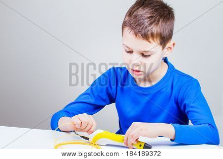 Kid drawing with 3d printing drawing pen. Creative, leisure, technology education concept