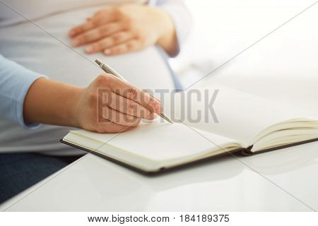 Young Pregnant Woman Writes To Her Diary On A White Table