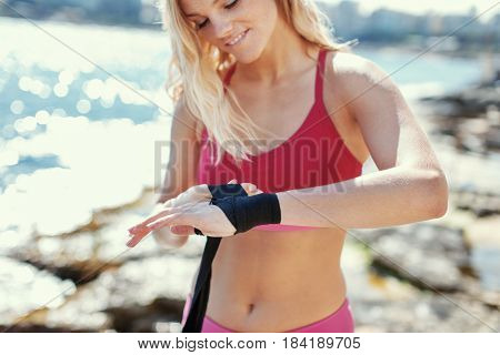 Blonde woman kickboxer wraps hand outdoor at sea