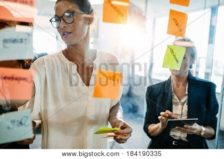 Portrait of creative professionals looking over a post it note wall and discussing. Female executives standing at the office behind glass wall with sticky notes.
