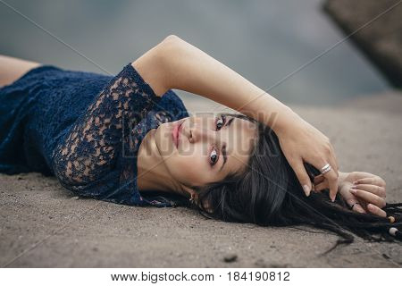 Lifestyle portrait of a woman brunette on background of the lake lying in sand on a cloudy day. Romantic gentle mystical pensive image of a girl. Girl Oriental appearance dreams of lying on sand