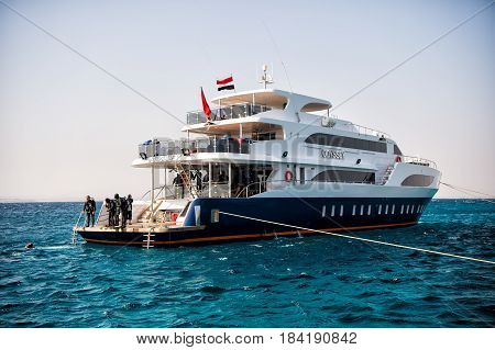 Hurghada Egypt - February 24 2017: white ship or yacht modern motor boat and group of people scuba divers in wetsuits snorkels in blue sea on summer day on clear sky. Snorkeling activity