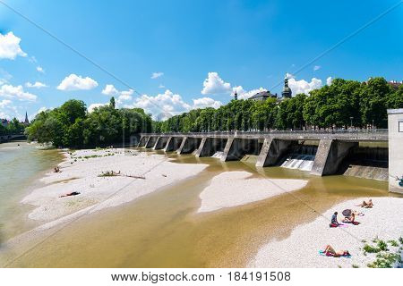 Munich, Germany - June 7, 2016: People enjoy sunny hot weather on the river banks of Isar river in bavarian city Munich. The river becomes a giant beach during hot days.