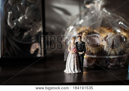 The statuette of bride and groom stands on the table