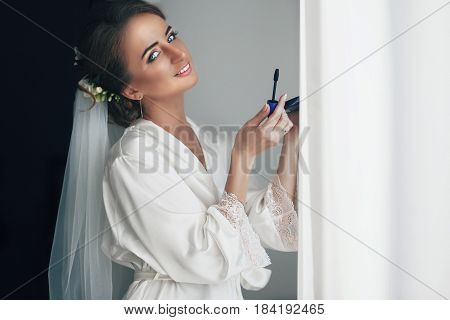 The smilling bride keeps a mascara stands in the room