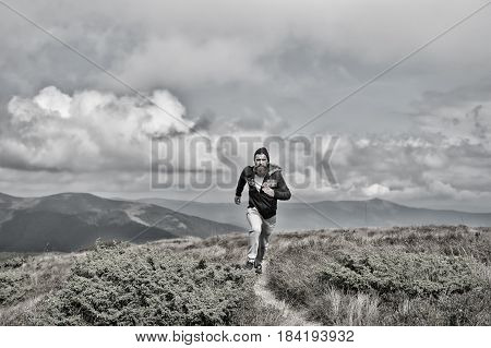 running. man runs on the green meadow in mountain on cloudy sky background
