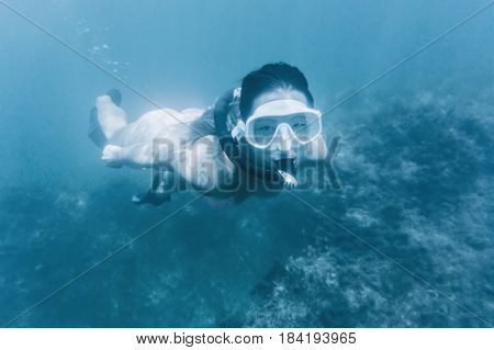 Young woman snorkeling in deep blue sea among seaweed looking at camera.