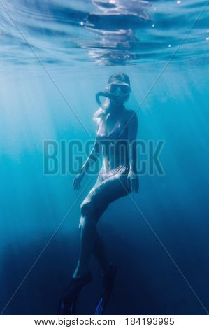 Beautiful young woman free diver swimming underwater surface among sunbeams.