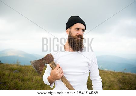 man long beard brutal caucasian hipster with moustache holds axe with serious face on mountain top with cloudy sky unshaven bearded guy with stylish hair getting beards haircut on natural backdrop