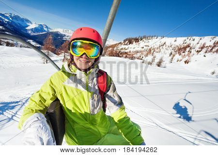 Happy young woman riding up to the start of slope on chairlift enjoying beautiful mountain scene