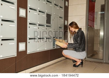 Young woman taking correspondence from mailbox sitting on her hunkers at doorstep