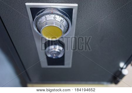 Closeup of top view combination safe with yellow knob and keyhole