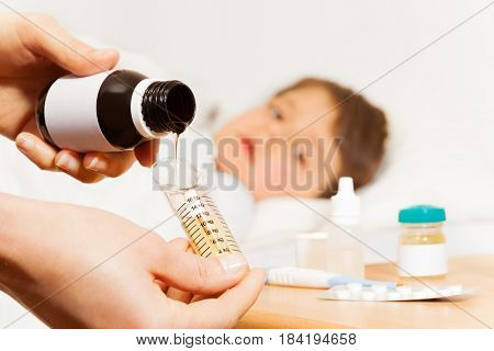 Female hands pouring antipyretic syrup from bottle with copy-space to metering spoon for sick boy