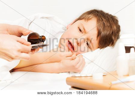 Sick kid boy laying in bed and crying while mother pouring coughing syrup from bottle with copy-space to metering spoon