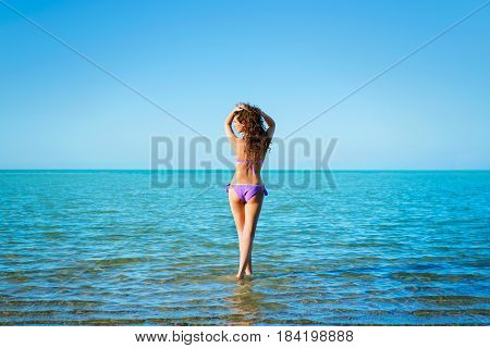 Young beautiful lady with curly hair atanding in water and looking far against blue sky background