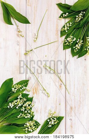 Lily of the valley on white wooden background.