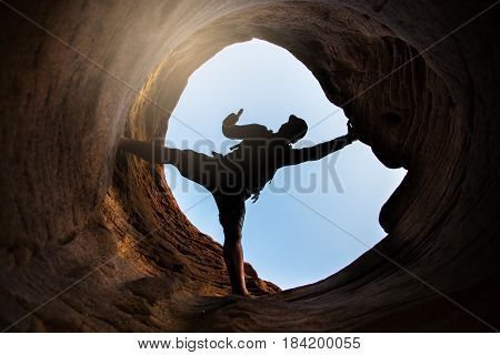 Young man climbing the mountain ridge at Sam Phan Bok, Ubon Ratchathani in Thailand Summer season